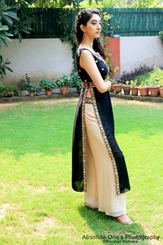 Black straight kurta with a yoke and side slits paired with straight loose beige pants.