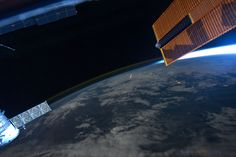 Earth from International Space Station with meteor visible and solar array at right