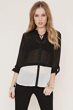 A woven blouse featuring a split neckline, a buttoned front, button-tab long sleeves, and a textured woven contrast panel along the hem.