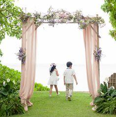グリーンの中に差し色になるよう、落ち着いたローズピンクのシフォンをあしらったアーバー。装花も繊細な淡い色合いで、ふたりをふんわり包み込んで