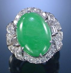 JADEITE AND DIAMOND RING, 1930S The central oval cabochon jadeite within a mount of radiating geometric design set with single-cut and baguette diamonds, size N ½, accompanied by a case from Harrods, London.