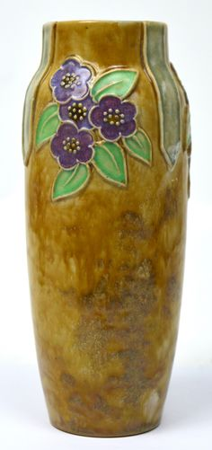 An unusual Royal Doulton mottled treacle baluster vase with floral relief decoration, Winnie Bowstead, various impressed marks to underside, numbered X8965B 15839, height 23cm. £20-40 est