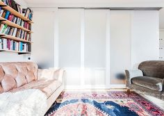 In this small one-bedroom Manhattan apartment, a clever couple used a bright Persian rug perfectly coordinated to their blush leather sofa to visually separate the living room from the master...