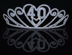 She�ll be the bell of the ball in this Sparkle Tiara 40.  Help the 40th birthday girl celebrate her big day with an age specific accessory.  Glitter covered tiara has beautiful swirls along the body and the number �40� above a heart on the center of the fun headpiece.  Everyone will know that it is her special day when she wears her tiara.  Combs are affixed to each end for ease in wearing.  Sold individually.