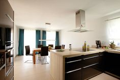 Beautiful modern kitchen with black cabinets and light wooden bench tops. By FingerHaus GmbH