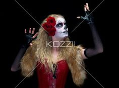 woman with traditional folk art posing with hands raised. - Image of a scary woman wearing sugar skull face make-up posing against dark background with hand raised. Model: Christine Vandenberk