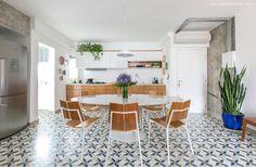 Cozinha integrada tem piso de ladrilho hidráulico e mesa saarinen