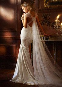 Dramatic and elegant, you will be the perfect bride in this sensational satin gown!  Satin soft tulle cap sleeve slim gown with a glamoroustulle back train.  Antique leaf detailadnores theneckline and back of gown for a truly stunning look.  Sweep train. Sizes 0-14.  Available in stores in White and Ivory.  Fully lined. Back zip. Imported polyester. Dry clean  Petite: Style 7SPK472. Sizes 0P-14P.  (special order only). Woman: Style 9SPK472. Sizes 16W-26W.  (special order only).