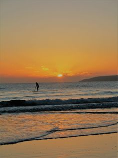 waves curling on to the shore with a paddleboarder in the sunset over  the seahttp://ednoveanfarm.co.uk/blog/a-walk-with-the-sunset/