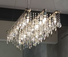MBeagle's Tip: Line up two to three LINEAR CHANDELIERS parallel to one another to get this look.  There are a lot of linear chandeliers at good price points at Overstock and Houzz.