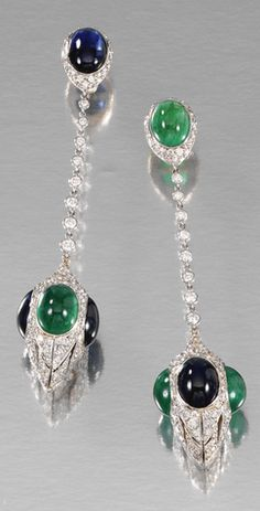 PAIR OF EMERALD, SAPPHIRE AND DIAMOND EAR PENDANTS Each surmount embellished with a cabochon sapphire and emerald respectively, suspending a chain of spectacle-set brilliant-cut diamonds and terminating on a fluted drop dressed with oval cabochon sapphires and emeralds and brilliant-cut diamonds, post and butterfly fittings.