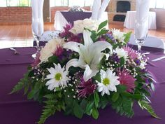 Centros de mesa con lirios, rosas y margaritas.