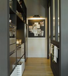 source: El Mueble Modern kitchen pantry with framed magnetic chalkboard with picture light, gray walls and gray built-in cabinets. Kitchen Pantry, Kitchen Dining, Kitchen Decor, Dining Room, Dining Area, Organized Kitchen, Narrow Kitchen, Compact Kitchen, Dinning Table