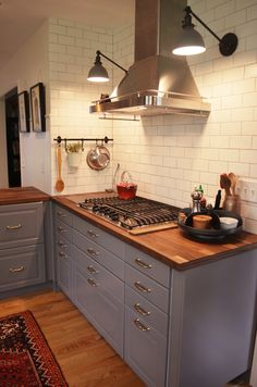 Schoolhouse electric sconces over gas range. Matte white subway tile. Lighted spice drawers under range.