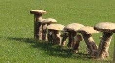 Idea for this: pieces of log partially buried in the ground with rings of log fitted on to the top?