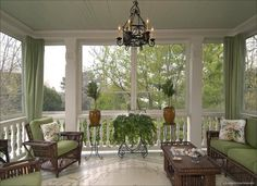 A gorgeous screened porch with beautiful flooring and elegant furniture in dark wicker and pale green.