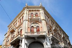 Photo taken in Piazza delle Erbe in Padua in Veneto (Italy). In the picture you see the little place next to the south, parts of the facades that look, respectively, to the east and west of the great, old and beautiful building of Debite. Above the arcades, with curtains, the floor you see a balcony with a mullioned window and semicircular frame, another smaller upstairs balcony and over the edge of the roof two lions and the blue sky.