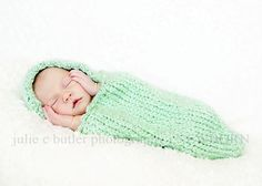 Soft acrylic knitted baby cocoon with hood. Photo prop for newborn baby.Cocoon measures 19 inches in circumference and 20 inches in length, with a nice stretch quality. Knitted using worsted weight acrylic. Hood is attached and frames the face with a delicate single crochet edging. For best results, hand wash cocoon with gentle detergent and lay flat to dry on a towel.Cocoon can be used to swaddle baby or as a photo prop. Do Not Leave Baby Unattended inside cocoon. $28.00
