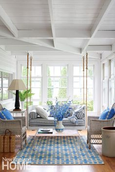"""To boost the ambience in the personality-filled porch along the front of the house, homeowner and designer Leslie Rylee paired the swing (devised with help from Kay Sloan, a friend whom the designer labels """"jack of all trades, seamstress, and facilitator extraordinaire"""") with old-time treasures like antique lamps and an end table decorated with wooden spools."""