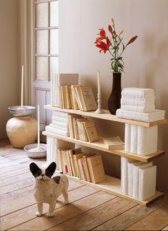 Livres recouverts de bandes de plâtres et placés entre des planches de bois pour former des étagères.