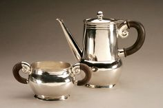 A beautiful Arts and Craft teapot and sugarbowl, with rosewood handles attached with silver rivets, and a conch shell motif, inspired by an Aztec design. These are from the Spratling First Design Period (1931-1946), and have the WS Print circle hallmark and Sterling mark. Spratling was an American architect who settled in Taxco, Mexico, and revived the art of silversmithing there.