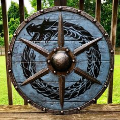 Authentic battleworn Viking shield with Ouroboros design and 6 simulated forged iron spikes.