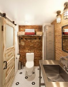 Salvaged Decor Shapes Small Industrial Bathroom With Exposed Brick Walls
