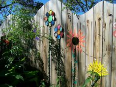 Flowers painted on the fence and ones made with paint can lid petals.