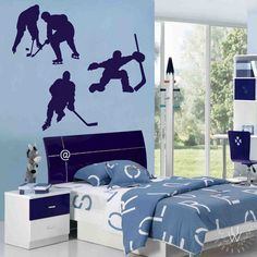 Three dark navy ice hockey walls decals placed on a light blue wall above a kid's bed and nightstand. Each decal displays a different hockey scene: a goalie, a player skating, and two players at a stand-off.