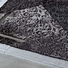 Nerocuoio // Venice - Sheepskin Rug - Soft and beautiful black natural fur rug, made of Mutton Hides with a laser carved floral pattern throughout. Merino Mutton Border and metal reinforcement on corners.  Passerinicasa.com