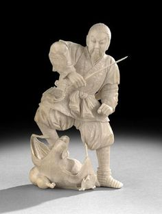 """Japanese Carved Ivory Okimono, 20th century, carved in high relief as a samurai holding a sword with one foot on the large figure of a bat with inset eyes, the bat grasping the samurai's leg, h. 6-1/2""""."""