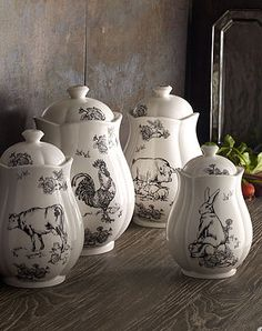 J Wilford Barnyard Toile Canister Set: Ivory lidded canisters in four sizes are adorned with decals depicting idyllic scenes of barnyard animals, designed by the artist E. Trostli. Imported. Large canister is 4