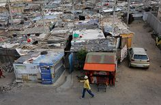 A man walks between some of the thousands of shacks that make up the township of Alexandra. Credit: Kim Ludbrook/EPA