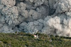 Close Encounter by Adam Stinton.  The rolling, boiling clouds of ash from a pyroclastic flow in the Belham Valley dwarf the Waterworks Estate house. This pyroclastic flow, which travelled 6 km down the valley in 11 minutes, was generated by an explosion that sent an ash plume 6 km into the atmosphere.