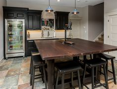 This #wetbar includes a #stainlesssteel beverage #fridge and unique #lightfixtures.