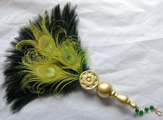 "Catriona Renaissance Feather Fan www.sapphireandsage.com  Sleek and shiny hackle feathers in a vibrant hue, sure to draw attention wherever you go! This rooster feather and peacock eye Renaissance fan showcases a hand-crafted wooden handle, topped with a 1.25"" floral motif wood medallion."