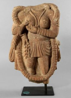 A Kushan Pink sandstone Torso of a YakshiMathura region1st/2nd CenturyThe goddess standing and holding a leafy branch in her right hand, her left hand cupping her right breast and suckling a bird perched on her right arm, and wearing a loin cloth, thick floral garland, ribbed cuffs and necklaces31.1cm high