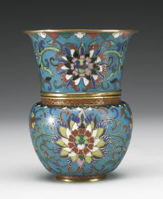 A CLOISONNE WINE CUP AND AWARMER  QING DYNASTY, 19TH CENTURY the footrim of the cup fitting snugly into the mouth of the associated bulbous warmer, the cup with flaring sides rising to a gilt rim, the exteriors of both decorated with similar lotus blossoms against a scroll-filled ground (2)  Height 4 1/2  in., 11.4 cm