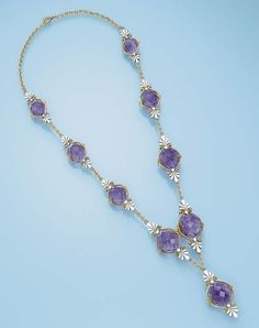 AN ANTIQUE AMETHYST AND ENAMEL NECKLACE   Designed as nine briolette-cut amethysts each within a gold scrollwork frame with white enamel palmette-motif finials to the gold link spacers and back, circa 1900, 57.0 cm long