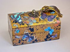 """Decoupage jewelry box. Please contact me BEFORE PURCHASING to find out the correct shipping costs. This gorgeous! decoupaged Butterfly box features an antique brass rosette and silk tassel. It is hand painted inside and out and seems to be flickering with all manner of beautiful butterflies that have been decoupaged on the surface. The box is 6"""" x 3 3/4"""" x 3 1/2"""" tall. It stands on its own as a beautiful decorative box, or can be used to store jewelry, loose change or anything else you…"""