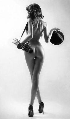 Фото Обнаженная девушка со шляпой и фотоаппаратом стоит к нам спиной (© zmeiy), добавлено: 02.08.2015 09:57
