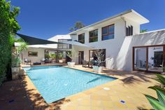 White two-story L-shaped home with simple backyard pool with wrap-around patio.