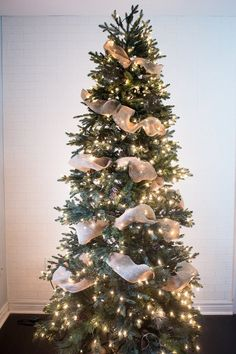 How to Put Ribbon Garland on a Christmas Tree A ribbon is the perfect solution to concealing those bare spots in your Christmas tree while also adding a touch of color and texture. Christmas Tree Ribbon Garland, Unique Christmas Trees, Alternative Christmas Tree, Christmas Tree Themes, Noel Christmas, Rustic Christmas, Xmas Decorations, Xmas Tree, Christmas Lights
