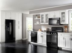 The black appliances make this stylish and sleek modern kitchen in white with glass cabinets