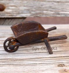 """Cute as a button! Add this miniature wheelbarrow to your fairy gardens or other small gardens. Made of cast iron and can be placed indoors or out. Measures 4.2"""" long."""