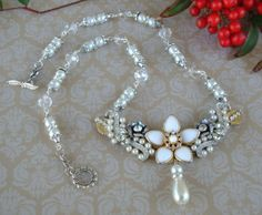Wedding Necklace .. A Necklace blank was used and attached to it are vintage findings, rhinestones, flowers, leafs, pearls and a beautiful focal flower, dangling at the center is a tear drop pearl .. Clear glass beads, pearls, rhinestone rondelles, bead caps and silver plated components complete this beautiful necklace FOR SALE .. $55.00