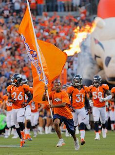 Players of the Denver Broncos run onto the field prior to the start of the game against the Pittsburgh Steelers during the NFL season opener at Sports Authority Field at Mile High on September 9, 2012 in Denver, Colorado.