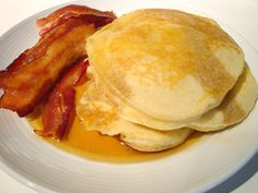 Lofty Buttermilk Pancakes, served with maple syrup and bacon.