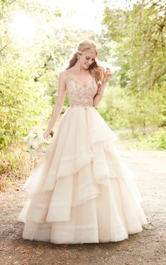 Flirty and feminine, this pink wedding dress with rose gold beading is a dream come true for the modern princess bride! The bodice of this Tulle gown features soft, scroll beadwork that extends through the straps on to the scoop back, giving the illusion the straps are floating. Pearl beads are scattered throughout, adding to the feminine style. A full, tiered ball gown skirt gives this wedding dress a glamorous feeling, while a full train completes the look. The back of this gown zips up…