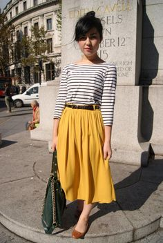 A white and black horizontal striped long sleeve t-shirt and a mustard pleated midi skirt will convey a carefree, cool-girl vibe. Add brown leather flats to your look for an instant style upgrade.   Shop this look on Lookastic: https://lookastic.com/women/looks/long-sleeve-t-shirt-midi-skirt-ballerina-shoes/15151   — White and Black Horizontal Striped Long Sleeve T-shirt  — Black Leather Belt  — Mustard Pleated Midi Skirt  — Dark Green Leather Tote Bag  — Brown Leather Ballerina Shoes